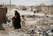 Internal displaced people (IDPs) walk past rubbish dumped in the street at a makeshift camp near Chikook suburb of north-west Baghdad, Iraq, July 23, 2009. - Boris Heger - 23-07-2009