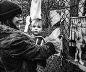 Woman pinning pictures of their families on the fence of Greenham Common, Embrace the Base protest, 1982 30,000 woman joined hands around the nine mile perimeter fence of RAF Greenham - Bob Naylor - 1980s,1982,activist,activists,adult,adults,against,anti,Anti Nuclear weapons,Anti War,Antiwar,armed forces,babies,baby,CAMPAIGN,campaign for nuclear disarmament,campaigner,campaigners,CAMPAIGNING,CAMP
