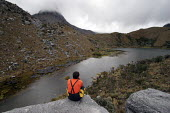 A walker sitting above a lagoon on the footpath to the mountain range of El Cocuy, culminating at a height of 5400 meters, Colombia. The region, not far from the border with Venezuela, used to be out... - Boris Heger - 2000s,2007,altitude,americas,armed,border,colombia,Colombian,Colombians,eni environmental issues,footpath,footpaths,Guerilla,Guerillas,Guerrilla,Guerrillas,height,holiday,holiday maker,holiday makers,