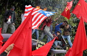 Protesters holding red leftists banners burn an american flag as President Bush meets his colombian counterpart Alvaro Uribe, in Bogota, March 11, 2007, Colombia. - Boris Heger - 11-03-2007