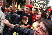 A man wearing a t-shirt representing venezuelan President Hugo Chavez protests in front of riot policemen as President Bush meets his colombian counterpart Alvaro Uribe, in Bogota, March 11, 2007, Col... - Boris Heger - 11-03-2007