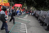 Protesters flags red leftist banners as they force their way in an attempt to reach the city center where President Bush meets his colombian counterpart Alvaro Uribe, in Bogota, March 11, 2007, Colomb... - Boris Heger - 11-03-2007