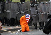 Colombia protester dressed as one of the Guantanamo Bay inmates kneeling in front of a line of riot policemen as President Bush meets his colombian counterpart Alvaro Uribe, in Bogota, March 11, 2007,... - Boris Heger - 11-03-2007