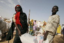 People displaced by the violence receive grain at a Red Cross food distribution, IDP camp of Gereida, Darfur region, Sudan, May 2006. - Boris Heger - 06-05-2006
