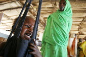A child displaced by the violence is being weighed at a malnutrition rehabilitation center as her mother watches him, IDP camp of Gereida, Darfur region, Sudan, May 2006. - Boris Heger - 06-05-2006