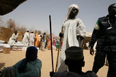 A policeman from the African Union watches on as people receive food at a distribution point, IDP camp of Gereida, Darfur region, Sudan, May 2006. - Boris Heger - 06-05-2006