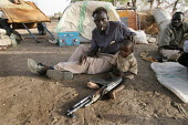 A drunk rebel fighter visiting his family displaced by the violence holds his baby, near the IDP camp of Gereida, Darfur region, Sudan, May 2006. - Boris Heger - 06-05-2006