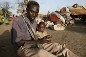 A drunk rebel fighter visiting his family displaced by the violence holds his baby, IDP camp of Gereida, Darfur region, Sudan, May 2006. - Boris Heger - 06-05-2006