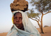 A woman displaced by the violence carry a stone on her head in the traditional way, IDP camp of Gereida, Darfur region, Sudan, May 2006. - Boris Heger - 06-05-2006