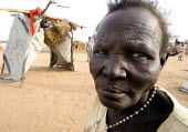 A woman displaced by the violence in front of her shelter, IDP camp of Gereida, Darfur region, Sudan, May 2006. - Boris Heger - 2000s,2006,age,ageing population,agencies,agency,aid,assistance,camp,camps,charitable,charities,charity,displaced,displacement,elderly,EQUALITY,excluded,exclusion,FEMALE,genocide,giving,HARDSHIP,help,