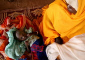A mother displaced by the violence cools down her baby making some wind. at a malnutrition rehabilitation center, IDP camp of Gereida, Darfur region, Sudan, May 2006. - Boris Heger - 07-05-2006