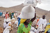 A woman carry sacks of seeds and grain at a food distribution, near Abata, at the foot of the Djebel Mara mountain range, Darfur region, Sudan, May 2006. - Boris Heger - 15-05-2006