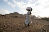 A beneficiary comes back from a food distribution, near Abata, at the foot of the Djebel Mara mountain range, Darfur region, Sudan, May 2006. - Boris Heger - 15-05-2006