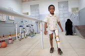 War wounded child learning to walk with his new orthopaedic prosthesis as his mother watches on in background, state orthopaedic center, Khartoum, Sudan, 2006 - Boris Heger - 27-05-2006
