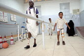 A war wounded child learning to walk with his new orthopaedic prosthesis as his mother watches, orthopaedic center, Khartoum, Sudan, 2006 - Boris Heger - 28-05-2006