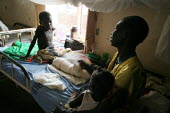 A boy rests on his bed as her mother watches on, in the childrens ward, Juba Teaching Hospital, South Sudan, May 2006. - Boris Heger - 25-05-2006