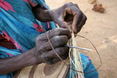 A woman refugee from Darfur prepares a traditional basket in the Gaga refugee camp, Eastern Chad, near the border with the Darfur region of Sudan. October 2005. - Boris Heger - 30-09-2005