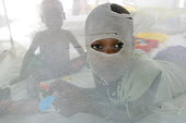 A South Sudanese war wounded boy watches through a hole in his mosquito net, in the Red Cross Lopiding Hospital, Lokichokio, Northern Kenya, December 2003. The hospital was the main medical facility f... - Boris Heger - ,2000s,2003,Africa,africans,agencies,agency,aid,aid agency,animal,animals,assistance,boy,boys,care,charitable,charities,charity,chemical,chemicals,child,CHILDHOOD,children,closed,closing,closure,closu