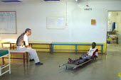 A South Sudanese war wounded waits to be checked with X-rays by a doctor as both of them wait for the machine to be repaired, at the Red Cross Lopiding Hospital, Lokichokio, Northern Kenya, December 2... - Boris Heger - 03-12-2003