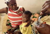 A mother and son, both AIDS sufferer receive their morning medication from a volunteer at the Centre dEspoir, outside Abidjan, Ivory Coast. The center is run by a swiss woman who used to be married to... - Boris Heger - 28-09-2002