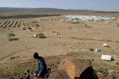 Refugee camp of Awr Aoussa, Djibouti, December 2003. A woman walks past tents and barbed wires. About 8500 asylum seekers from Ethiopia and Somalia have been brought by the authorities to this place i... - Boris Heger - 10-12-2003