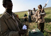 A villager casts his vote outside of a polling station as an armed local policeman watches on, in the village of Tadi, 45 km east of the regional capital city of Jijiga, Ethiopia, August 21, 2005. 1.5... - Boris Heger - 2000s,2005,47,adult,adults,african,africans,AK,AK 47,ak47,AK47S,armed,Armed Forces,Ballot Box,box,boxes,capital,CLJ,democracy,East Africa,election,elections,ethiopia,ethiopian,ethiopians,force,gun,gun