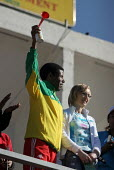 """World famous and recorder ethiopian athlete Haile Gebreselassie, one of the organizers of the """"Great Ethiopian Run"""", next to his wife, greets the 25,000 runners taking the start of the the biggest rac... - Boris Heger - 2000s,2005,Africa,african,africans,capital,East Africa,ethiopia,ethiopian,ethiopians,Great Ethiopian Run,male,man,men,people,person,persons,PHYSICAL,run,runner,runners,running,spo,sport,sports"""