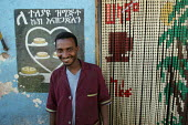 A waiter stands in front of a traditional pastry shop in the streets of the city of Harar, Ethiopia - Boris Heger - 2000s,2006,ACE,african,africans,architecture,arts,bought,buildings,buy,buyer,buyers,buying,cafe,cafes,catering,cities,city,color,colorful,colorfull,colors,COLOUR,colourful,COLOURS,commodities,commodit