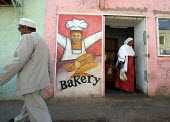 A woman comes out of a traditional bakery in the streets of the city of Harar, Ethiopia - Boris Heger - 2000s,2006,ACE,ace culture,African,Africans,architecture,arts,baker bakers,bakery,bought,bread,buildings,buy,buyer,buyers,buying,color,colorful,colorfull,colors,COLOUR,colourful,COLOURS,commodities,co