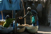 An old man buys some bread in the streets of the city of Harar, Ethiopia - Boris Heger - 05-02-2006