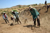 Villagers digging earth to construct a water point against drought, near Nazret, Ethiopia, 2006 - Boris Heger - 2000s,2006,african,africans,Afromontane,against,BUILDING,BUILDINGS,by hand,catchment,clean water,communities,community,construction,country,countryside,dig,digging,drought,East Africa,EBF Economy,eni