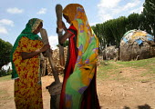 Woman pounding grain with a pestle and mortar in front of traditional somali style huts in the village of Hagadjin, 35 km from Jijiga, Ethiopia, on Sunday, August 28, 2005. - Boris Heger - 28-08-2005