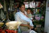 A mother and baby in the family shop, near Dire Dawa, Ethiopia, October 2005. - Boris Heger - 2000s,2005,adult,adults,african,africans,babies,baby,bought,boy,boys,buy,buyer,buyers,buying,CARE,carer,carers,child,childcare,CHILDHOOD,CHILDMINDING,children,commodities,commodity,communities,communi
