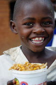 A pupil enjoys his only meal of the day, Kajiado school, Machakos rural area, Kenya, May 2004. Without food being given to children, most of them would not attend the classes as they would have to loo... - Boris Heger - 11-05-2004
