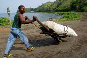 A man carrying goods in a hand made wooden cart pass by the lake Tanganyika, near Goma, Eastern Congo (DRC), May 2004. - Boris Heger - 18-05-2004