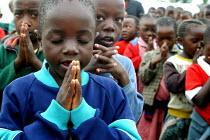 Pupils pray ahead of the start of the lessons, Mukuru school, Nairobi, Kenya, May 2004. - Boris Heger - 11-05-2004