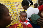 People recently returned from refugee camps in Guinea look at a tracing board set up by the International Red Cross to check if they recognise photographs of children who got lost during the war, near... - Boris Heger - 21-02-2006
