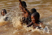 Children enjoy a bath in the river after heavy rain near Voinjama, near the border with Guinea, Lofa County, Liberia, February 2006. - Boris Heger - ,2000s,2006,adolescence,adolescent,adolescents,Africa,african,africans,bathing,border,boy,boys,child,CHILDHOOD,children,communities,community,EMOTION,EMOTIONAL,EMOTIONS,EXERCISE,exercises,happiness,ha