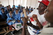 Members of the Nigerian Red Cross explain to pupils how to use a condom during a school workshop about HIV AIDS problems in Katsina, Nigeria 2006. - Boris Heger - 2000s,2006,Acquired immune,agencies,agency,aid,aid agency,AIDS,charities,charity,child,CHILDHOOD,children,con,condom,condoms,contraception,contraceptive,contraceptives,deficiency syndrome,DISEASE,DISE
