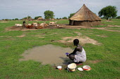 A Dinka woman washes dishes in front of her traditional hut, near Padak, South Sudan, April 2004. - Boris Heger - 2000s,2004,basic,clean,communities,community,country,countryside,dirty water,dishes,FEMALE,Grass,house,houses,housing,hut,huts,outdoors,outside,pans,people,person,persons,plates,pots,rural,scarce,scar