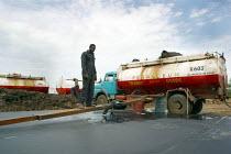 A driver fills a tank with petrol, near Padak, South Sudan, April 2004. - Boris Heger - 28-04-2004