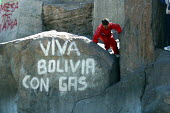A child plays around a stone with a long life to Bolivia with gas nationalist grafiti referring to the possible nationalisation of natural resources, La Paz, Bolivia, August 2004 - Boris Heger - ,2000s,2006,activist,activists,americas,Amerindian,Amerindians,bolivia,Bolivian,Bolivians,boy,boys,CAMPAIGN,campaigner,campaigners,CAMPAIGNING,CAMPAIGNS,child,CHILDHOOD,children,cities,city,DEMONSTRAT
