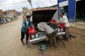 People repair an old car in Los Altos de Cazuca, one of the worst slums in Bogota, Colombia, January 2006. There are an estimated 3 million people displaced by conflict with guerrilla groups. - Boris Heger - 30-08-2006