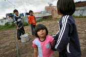 Displaced children get water from a hosepipe, as there is no running water in the houses. Los Altos de Cazuca, one of the worst slums in Bogota, Colombia, January 2006. There are an estimated 3 millio... - Boris Heger - 30-08-2006