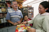 A girl buy some food in a shop in Bogota, November 2006. - Boris Heger - 2000s,2006,americas,Bogota,bought,business,buy,buyer,buyers,buying,child,CHILDHOOD,children,clJ crime law justice,colombia,Colombian,Colombians,commodities,commodity,consumer,consumers,customer,custom