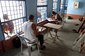 Detainees reading newspapers and writing to relatives, at the central jail, Quibdo, Colombia, August 2004. - Boris Heger - 30-08-2006