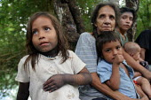 Internally displaced by FARC guerillas, an Embera indigenous family who used to live right on the border with Colombia, near Yaviza, Darien region, Panama, living in dire conditions in Arrevachi villa... - Boris Heger - 2000s,2006,adult,adults,age,ageing population,americas,Amerindian,Amerindians,armed,BAME,BAMEs,BME,bmes,Boca de cupe,border,boy,boys,Cana,child,CHILDHOOD,children,Colombia,communities,community,countr