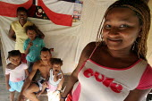 Colombian refugees displaced by the civil war in their country in their new house, whith a Panamean flag in background, Boca de Cupe, Darien region, Panama, January 2006. This region is very remote. - Boris Heger - 30-08-2006
