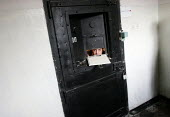 A detainee sentenced takes a glimpse out of his cell through the aperture used for food deliveries, central prison, Yerevan, Armenia, February 2005. The red point on the right side of the door means t... - Boris Heger - 28-02-2005