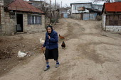 Old woman passing by in the street of Azokh, Nagorno Karabakh, Azerbaidjan, March 2005. The region, although officially located within Azerbaidjan, is being occupied by Armenia and has became a de fac... - Boris Heger - 04-03-2005